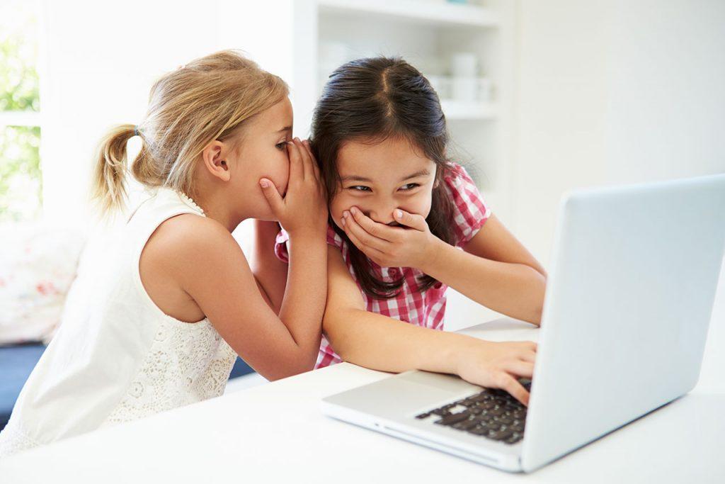 Zwei Junge Mädchen am Laptop. Das Mädchen links flüstert ihrer Freundin etwas ins Ort, die mit vor Mund gehaltener Hand lacht