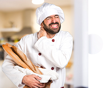 Arbeitssicherheit - Bäcker mit Baguettes im Arm, der sich schmerzverzerrt in den Nacken fässt