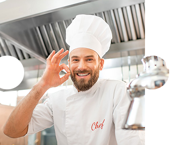 Lebensmittelhygiene - lächelnder Koch in der Gastro-Küche, der mit der rechten Hand das Zeichen für OK signalisiert