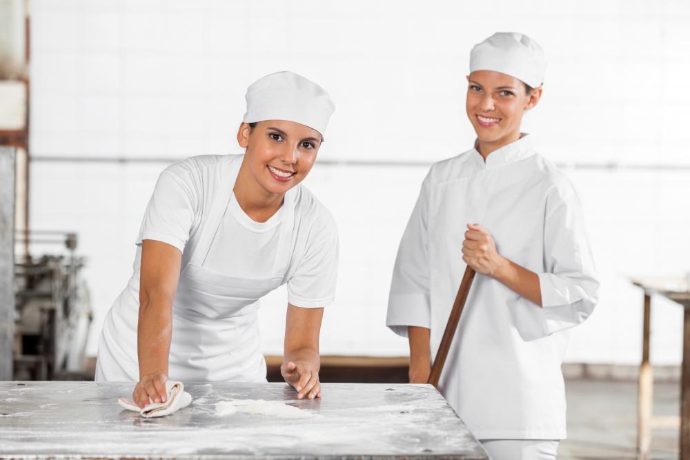 Zwei Bäckerinnen, ganz in weiß und mit Haarnetz beim Saubermachen der Backstube